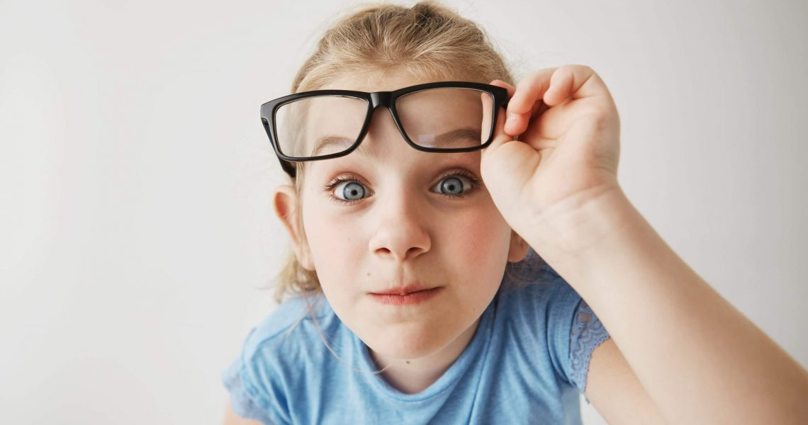 Close up portrait of cheerful small girl with blonde hair and blue eyes funny imitates adult person with glasses with surprised expression