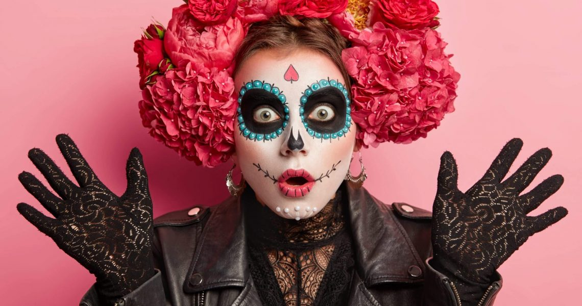 Close up shot of shocked woman wears frightening makeup, keeps palms raised, celebrates Halloween or Mexican Day of Death, isolated over pink background, scared by something. Art and face painting