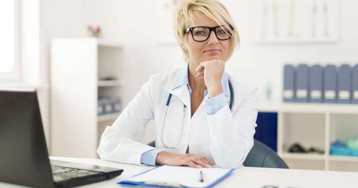 Portrait of beautiful young female doctor in office